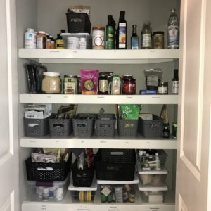 Pantry with items in bins and labeled shelves